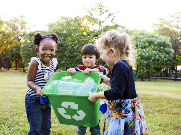three children laughing and holding a recycling bin containing plastic water bottles