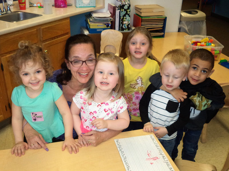 Care A Lot child care center showing a staff member smiling surrounded by five children